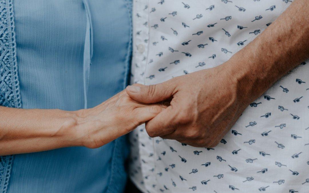 older couple holding hands together