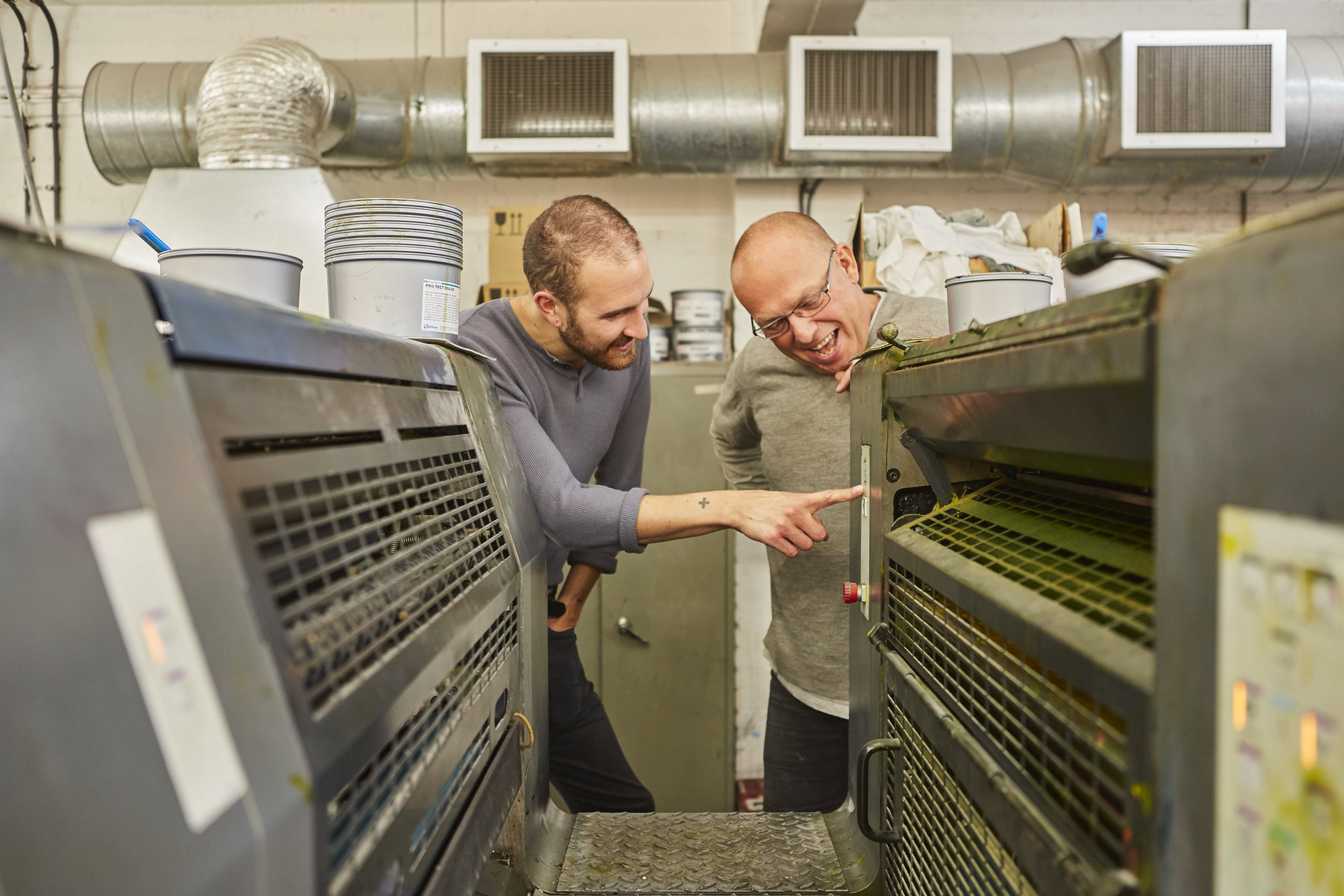 two men looking at a print machine