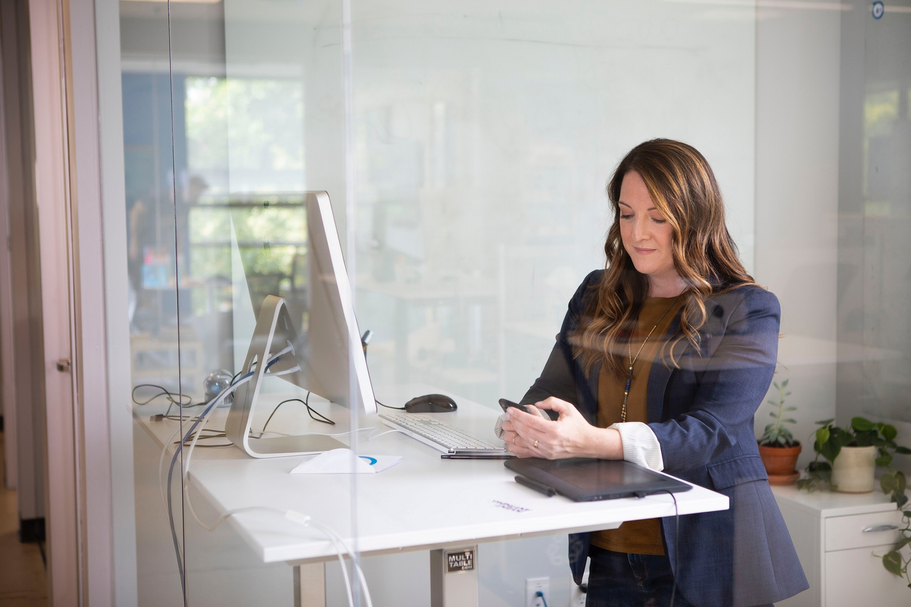 woman at computer desk on the phone looking at her mobile