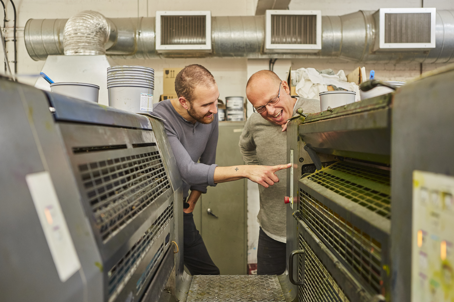 two men looking at a printing machine